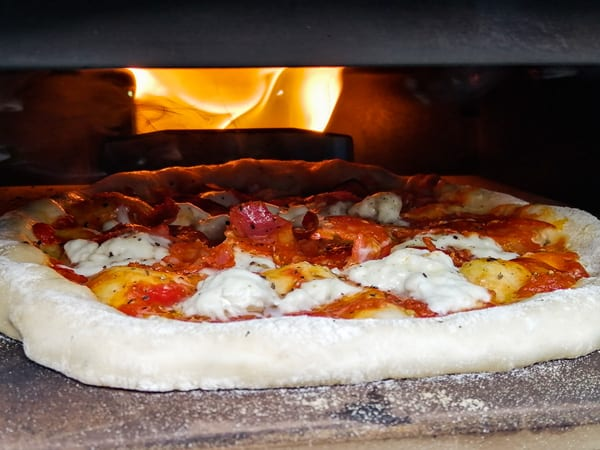Pizza cooking in a portable pizza oven