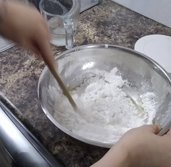 Mixing Neapolitan pizza dough with spoon