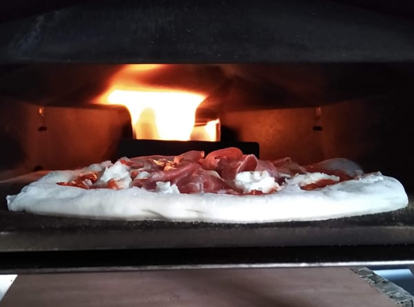 Cooking Neapolitan pizza in wood fired oven