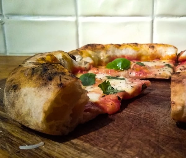 The thin base and light airy crust of Authentic Neapolitan pizza
