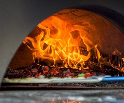 Neapolitan pizza being loaded into large wood fired oven